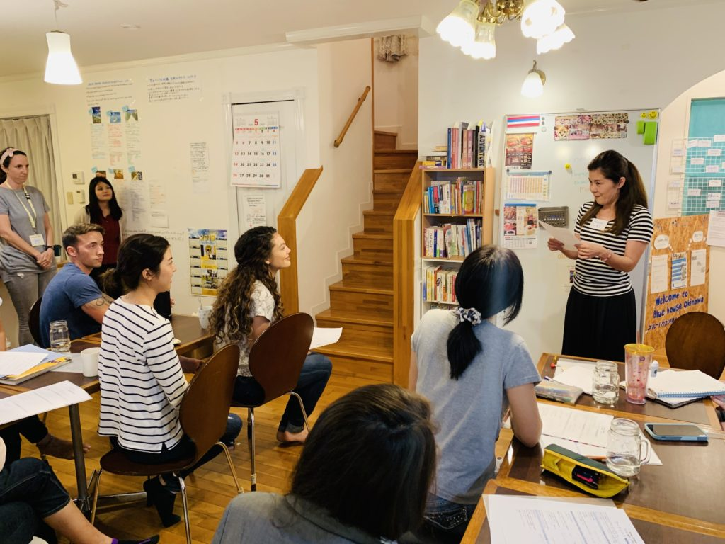 A group of Japanese and English language students practicing speeches during a language exchange event